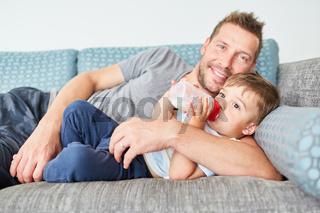 Vater füttert Kleinkind mit Milch aus der Flasche