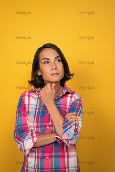 Thoughtful woman looks up at copy space on right side while touhing her chin with hand. Isolated on yellow background in studio