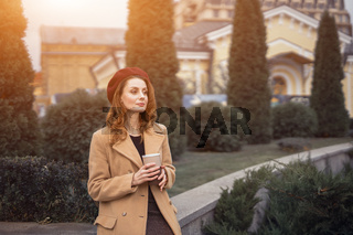 Pensive beautiful young woman holding a cup of coffee on the street female fashion. Portrait of stylish young woman wearing autumn coat and red beret outdoors. Autumn accessories