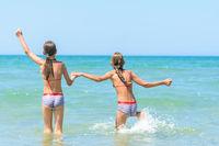 Sisters joyfully and happily run into the sea on a hot sunny day