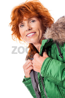 redhead smiling adult mature woman with geen warm jacket