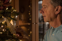 Senior adult man holding a christmas ornament and remembering the past