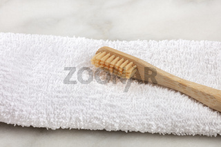 A closeup of an organic biodegradable bamboo toothbrush on a white towel