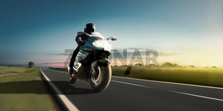 Rapid motorbike ride on the country road at the most beautiful sunset. Adventure and motor sport.