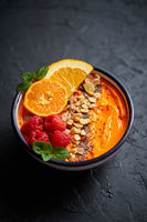 Bowl with fresh healthy smoothie or yogurt. With orange slices, tangerine, raspberry, chia and nuts