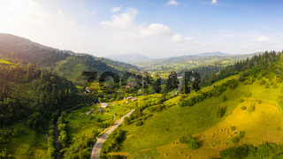 Scenic panoramic landscape. Aerial drone view of picturesque urban-type settlement in valley among green nature, coniferous forests, and Carpathians mountains. Popular tourists place