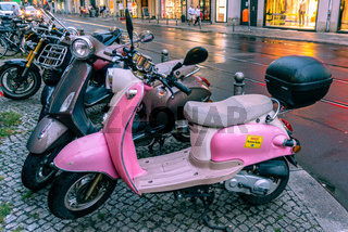 Scooters parked on the street in Berlin. Pink with retro look