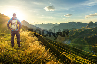 Man reaching summit enjoying freedom. Beautiful sunrise and layered mountain silhouettes in early morning. Lechtal and Allgau Alps, Bavaria and Austria.
