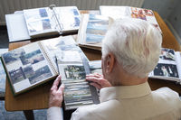 Top view of a senior man looking through old photo albums