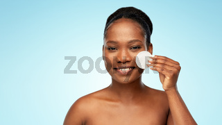 african woman cleaning face with cotton pad