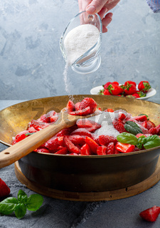 Cooking strawberry and basil jam.