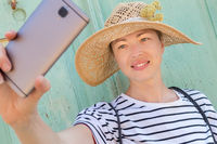 Beautiful young female tourist woman wearing big straw hat, taking self portrait selfie, standing in front of vinatage turquoise wooden door at old Mediterranean town.