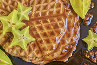 waffle with syrup and star fruit fresh on stone table