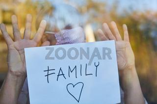 Seniorin hält Family Schild ins Fenster während Coronavirus Pandemie