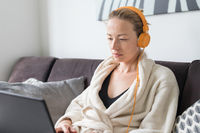 Stay at home, shelter in place and social distancing. Woman in her casual home bathrobe relaxing while working remotly from her living room. Using social media apps for video chatting.