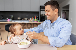 happy father feeding baby in highchair at home