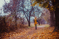 Woman walking in autumn park. Stylish girl wears black leather jacket, yellow dress and scarf outdoors.