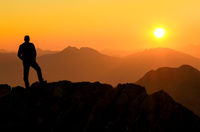 Happy success winning man standing relaxed on mountain at sunset. Border region of Tyrol, Austria and Allgaeu, Bavaria, Germany.