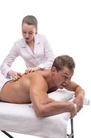 Masseuse doing massage on back of male client - cry for pain