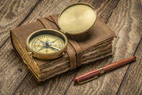 antique leather-bound journal with compass on rustic wood