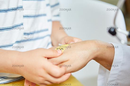 Kid sticks plaster on hand from pediatrician