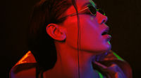Sensual portrait of girl wearing down jacket and sunglasses in neon color lights . Pretty girl in neon light on black background. Night club, Party