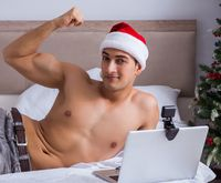 Sexy man in the bed wearing santa hat in christmas concept