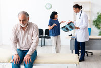 Old couple visiting young male doctor
