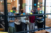 Diverse group of colleagues wearing face masks brainstorming at glass wall in office