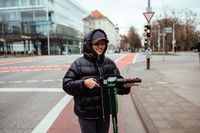 Beautiful young woman riding an electric scooter, street-style