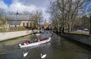 Boats with tourists on a canal in Bruges, Belgium.