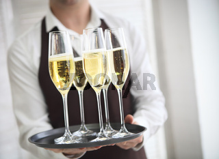 Professional male waiter in uniform serving champagne