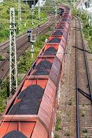 long coal train passes under a bridge in cologne