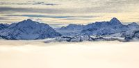 Snow covered mountains with inversion valley fog and trees shrouded in mist. Scenic snowy winter landscape in Alps at sunrise morning. Allgau, Kleinwalsertal, Bavaria, Germany.