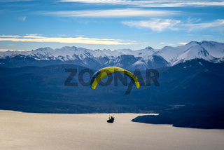 Paragliding over Nahuel Huapi lake and mountains of Bariloche in Argentina, with snowed peaks in the background. Concept of freedom, adventure, flying