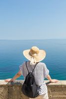 Rear view of woman traveler wearing straw summer hat and backpack,leaning against a stone wall looking at big blue sea and islands in on the horizon.