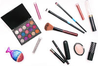 Makeup tools. Eyeshadow palette, mascara, face powder and brushes. Cosmetic accessories on a white background.
