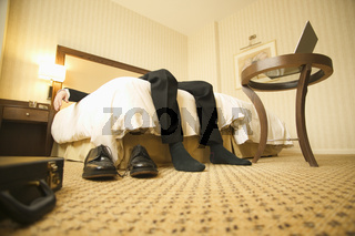 Businessman relaxing on hotel room bed