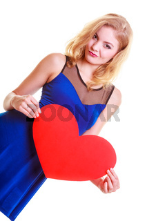 Red heart card. Love symbol. Portrait beautiful woman hold Valentine day symbol. Cute blonde girl in blue dress expressing tender feelings. Isolated studio shot