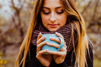 Girl wears knitted sweater and scarf enjoying hot drink outdoors in autumn.