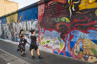 visitors in front of  east-side gallery murals