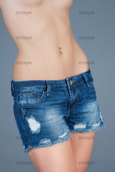 beautiful belly of a woman wearing blue jeans shor