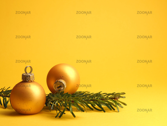 Two golden vintage Christmas baubles on a yellow background