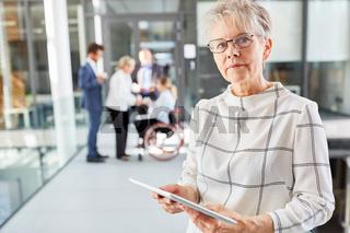Seniorin im Business Unternehmen mit Tablet Computer