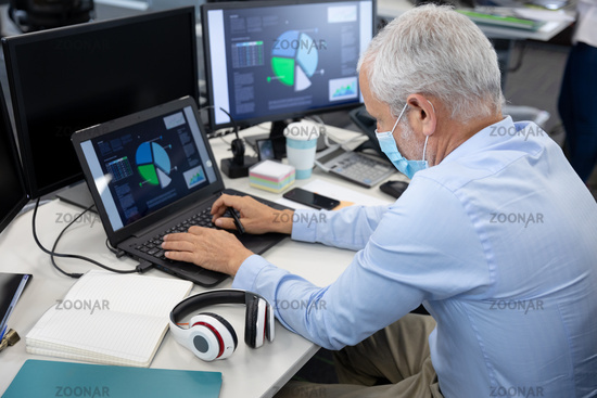 Senior businessman wearing face mask using laptop at modern office
