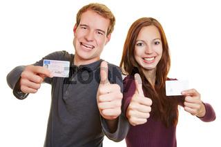 Mann und Frau mit Führerschein halten Daumen hoch