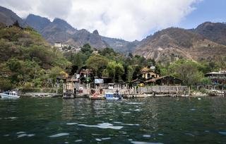 View from lake Atitlan to the coast with boat docks of the mountain village Santa Cruz la Laguna, Guatemala