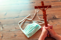 A child holds a wooden cross with a Jesus figurine next to a mouth mask