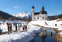 Cross-country skiers on sunny track along a river and a pitoresque church, Seefeld, Austria