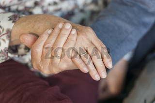 Hands of an 80 year old couple with rings